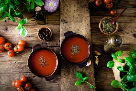 madera rústica: Sopa de tomate con aceite de oliva y albahaca. Comida vegetariana.