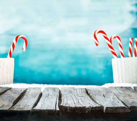 christmas display: Christmas background. Wooden table with candy cane on snow. Empty winter display for your montage