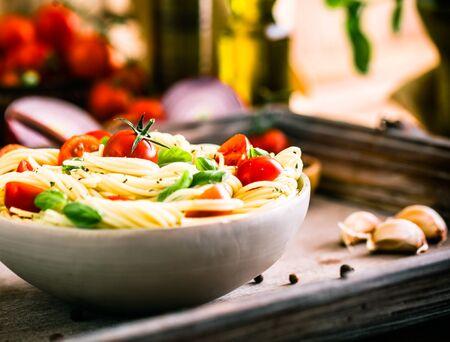 Cocina italiana. Pasta con aceite de oliva, ajo, albahaca y tomates. Espaguetis con tomates Foto de archivo