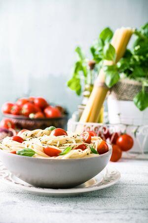 tomates: Cuisine italienne. P�tes � l'huile d'olive, l'ail, le basilic et les tomates. Spaghettis aux tomates Banque d'images