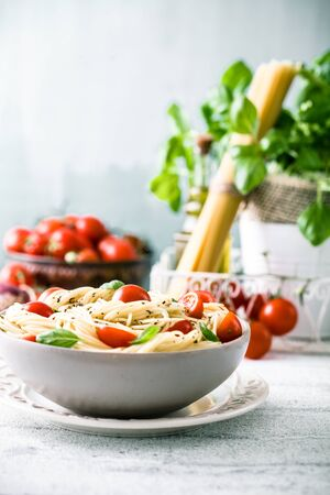 tomatoes: Italian cuisine. Pasta with olive oil, garlic, basil and tomatoes. Spaghetti with tomatoes