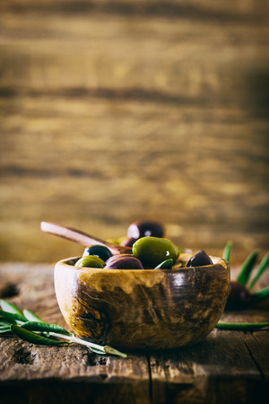 alimentation: olives on olive branch. Wooden table with olives in bowl