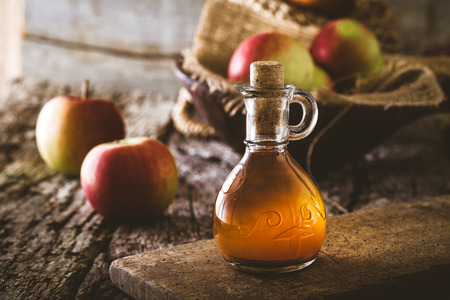 Apple vinegar. Bottle of apple organic vinegar on wooden background. Healthy organic food. Imagens - 55662812