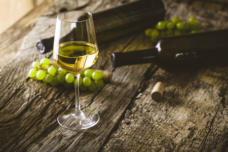 Wine. Glass of white wine in wine cellar. Old white wine on wood. Stockfoto