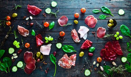 dark meat: Italian ham, prosciutto and salami. Ingredients for bruschetta, crostini or sandwich bar. Rustic top view of ingredients. Ham with vegetables and spices Stock Photo