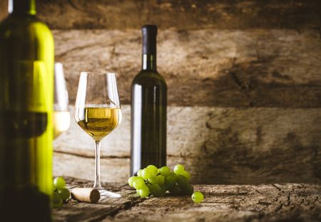 Wine. Glass of white wine in wine cellar. Old white wine on wood. Foto de archivo