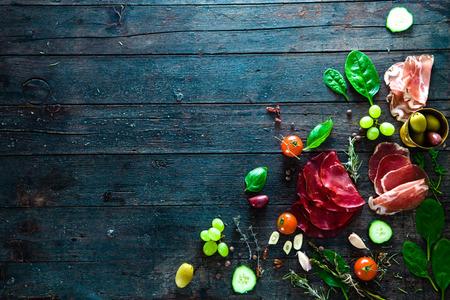 イタリアのハム、生ハム、サラミ。ブルスケッタ、クロスティーニまたはサンドイッチのバーなどの材料。食材の素朴な平面図です。野菜とスパイ