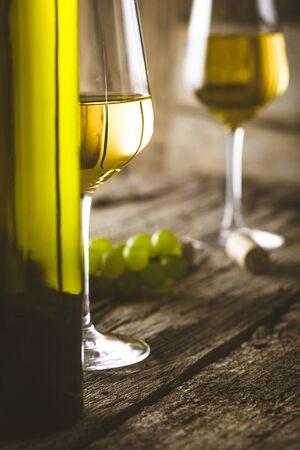 Wein. Glas Weißwein in einem Weinkeller. Alte Weißwein auf Holz.