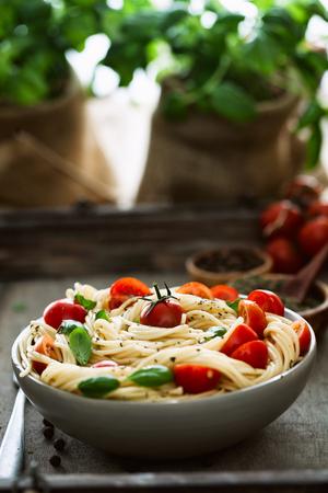 italian cuisine: Italian cuisine. Pasta with olive oil, garlic, basil and tomatoes. Spaghetti with tomatoes