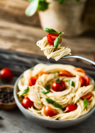 Italian cuisine. Pasta on fork. Pasta with olive oil, garlic, basil and tomatoes. Spaghetti with tomatoes Stock Photo