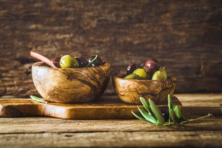 olives: olives on olive branch. Wooden table with olives in bowl