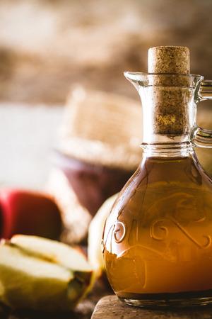 food dressing: Apple vinegar. Bottle of apple organic vinegar on wooden background. Healthy organic food.