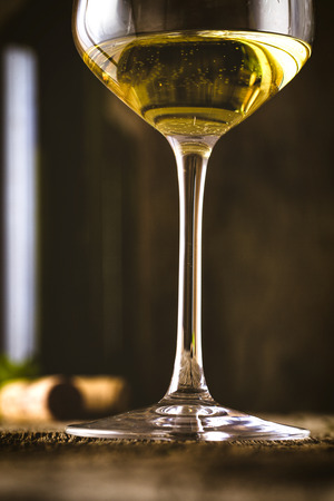 white red: Wine. Glass of white wine in wine cellar. Old white wine on wood. Stock Photo
