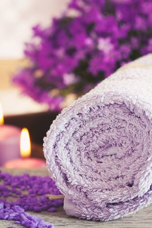 Natural wellness and spa setting with flowers and towel and water for treatment. Dayspa cosmetics products Stock Photo