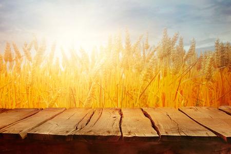 Weizenfeld mit hölzernen Planken. Leere Tischplatte. Tabelle mit Weizen. Schöne Natur-Sonnenuntergang-Landschaft. Ländliche Landschaft mit goldenem Weizen. Landwirtschaftshintergrund mit Ernte Standard-Bild - 81160812