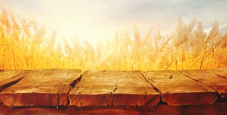 Weizenfeld mit hölzernen Planken. Leere Tischplatte. Tabelle mit Weizen. Schöne Natur-Sonnenuntergang-Landschaft. Ländliche Landschaft mit goldenem Weizen. Landwirtschaftshintergrund mit Ernte Standard-Bild - 81160818
