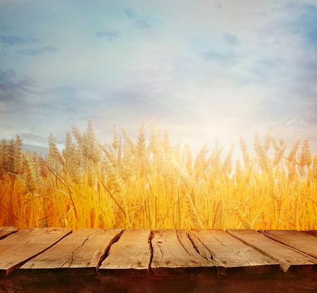Weizenfeld mit hölzernen Planken. Leere Tischplatte. Tabelle mit Weizen. Schöne Natur-Sonnenuntergang-Landschaft. Ländliche Landschaft mit goldenem Weizen. Landwirtschaftshintergrund mit Ernte Standard-Bild - 81160817
