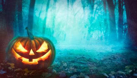 Halloween achtergrond. Spookachtig bos met dode bomen en pompoen. Halloween-ontwerp met pompoen Stockfoto
