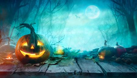 Halloween-pompoenen op hout. Halloween-achtergrond bij Nachtbos met Maan. Stockfoto