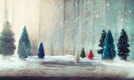 Christmas trees on wood. Christmas background with snow. Small xmass trees