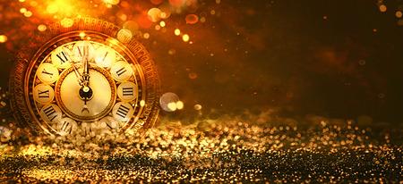 新年の背景。クロックカウントダウン。黄金の休日抽象的に輝く星との背景をデフォーカス。ぼやけたボケ。ぼやけた背景