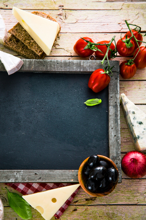 Italian cooking. Fresh ingredients with pasta for italian cuisine. Cheese variety on chalk board Stock Photo