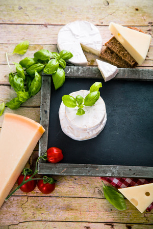 Italian cooking. Fresh ingredients with pasta for italian cuisine. Cheese variety on chalk board Zdjęcie Seryjne