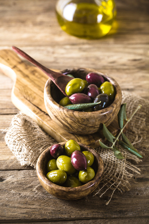 olives on olive branch. Wooden table with olives in bowl