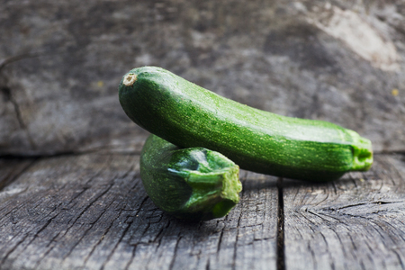 Vegetables background. Fresh green zucchini  on wood in vintage setting
