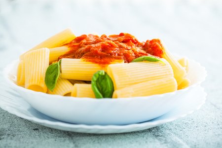 Pasta with Tomato Sauce and Basil on a Fork. Italian food. Mediterranean cuisine