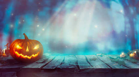 Halloween  with Pumpkin and Dark Forest. Scary Halloween Design on table Stock Photo