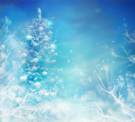 Winter frozen background. Winter Christmas concept with tree branches, snow and bokeh lights. Christmas tree in snow. Stock Photo
