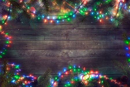 Christmas fairy lights on wood. Christmas background with string lights and pine tree. Fir branches