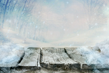Winter design. Christmas background with frozen wooden table with the landscape. Snow and ice on wooden table with snowy forest