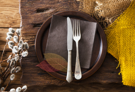 Spring table setting. Cutlery on wood. Fork and knife in plate. Flatlay overhead shot