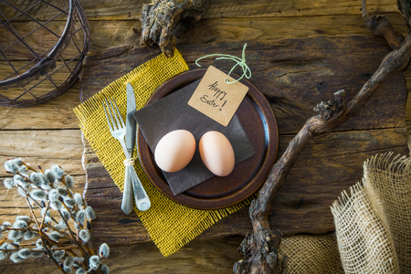 Easter table setting. Fresh eggs on plate. Spring table. Flatlay overhead shot Stock Photo - 117842911