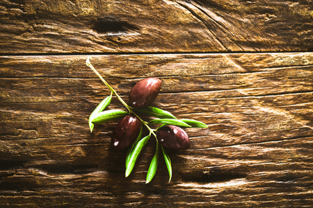 Olives on olive branch. Wooden table with olives. Old wood with olives Stock Photo
