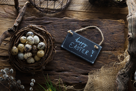 Easter table setting.Quail eggs in nest. Spring table. Happy Easter text on plate Stock Photo