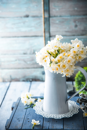Spring flowers on wood. Rustic spring setting. Narcissus flowers