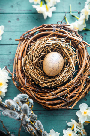Easter eggs on wood. Natural quail eggs. Easter holiday concept with  eggs in wisker basket in nature 스톡 콘텐츠