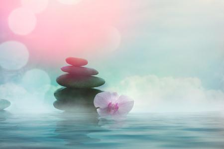Terme e benessere. Pietre da massaggio naturali con fiori di orchidea .Trattamento termale Archivio Fotografico