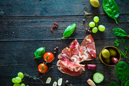Italian ham, prosciutto and salami. Ingredients for bruschetta, crostini or sandwich bar. Rustic top view of ingredients. Ham with vegetables and spices 스톡 콘텐츠