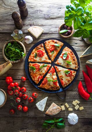 Pizza on wood with ingredients. Pizza with cheese, tomatoes and basil. Rustic italian pizza Reklamní fotografie