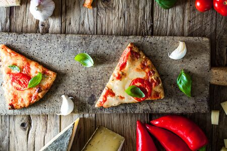 Pizza slice on wood with ingredients. Pizza with cheese, tomatoes and basil. Rustic italian pizza 스톡 콘텐츠