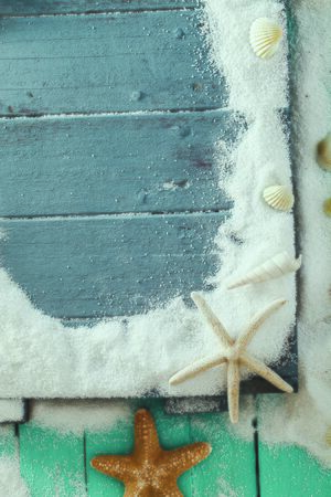 Summer background. Wooden background with white sand and seashells. Shells, starfish and sand. Holiday background