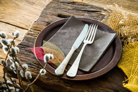 Spring table setting. Cutley on wood. Fork and knife in plate. Flatlay overhead shot