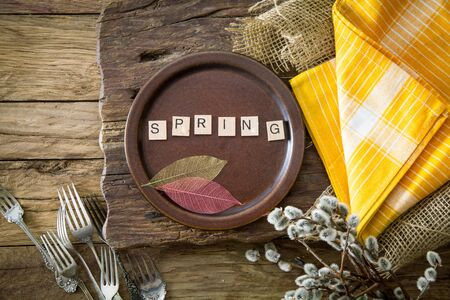 Spring table setting. Cutley on wood. Flatlay overhead shot. Wooden letters with spring text