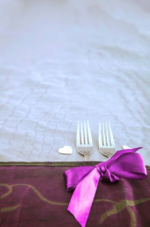 Valentines day table. Forks with purple ribbon. Gift for Valentine's day.St. Valentine table Standard-Bild