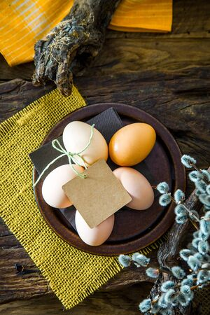 Easter table setting. Fresh eggs on plate. Spring table. Flatlay overhead shot