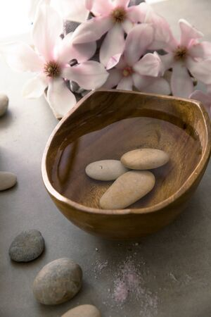 Spa and wellness. Natural massage stones , silkworm cocoon with magnolia flower .Spa treatment